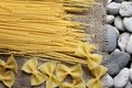 Spaghetti farfalle on burlap fray and the river rock Royalty Free Stock Photos