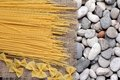 Spaghetti farfalle on burlap fray and the river rock Royalty Free Stock Photography