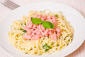 Spaghetti with ham cheese and basil on plate Stock Photography