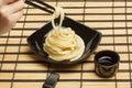Spaghetti macaroni in black ceramic plate with chopsticks at str Royalty Free Stock Photo