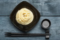 Spaghetti macaroni in black plate with chopsticks at wooden tabl Royalty Free Stock Photo