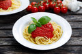 Spaghetti with marinara sauce and basil leaves on top, decorated with vegetables. on wooden table. Royalty Free Stock Photo