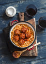 Spaghetti and meatballs in tomato sauce and two glasses with red wine on wooden rustic board.
