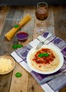 Spaghetti Pasta with Tomato Sauce, Chees and Basil with White Wine Glass on Wooden Table. Traditional Italian Food Royalty Free Stock Photo