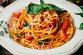 stock image of  Spaghetti pasta with tomato sauce, parmesan and basil on a white plate. The classic tomato spaghetti: vegetarian tomato basil
