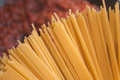 Spaghetti raw in a pot ready for cooking red sauce in the background Royalty Free Stock Photos