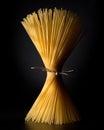 Spaghetti tied together on black Stock Photos