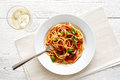 Spaghetti with tomato sauce, fresh basil and cheese. Glass of white wine and fork. From above. Royalty Free Stock Photo