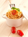 Spaghetti with tomatoes and basil in an earthenware pot Royalty Free Stock Image