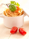 Spaghetti with tomatoes and basil in an earthenware pot Stock Photo