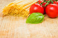 Spaghetti with tomatoes and basil on a wooden background fresh board Royalty Free Stock Images
