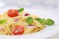 Spaghetti with tomatoes noodles pasta on a plate and basil Royalty Free Stock Photo