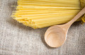 Spaghetti uncooked and spoon wood on gunny Royalty Free Stock Photos
