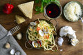 Spaghetti vongole bowl of surrounded by chili fruit parmasan pieces glass of wine grated parmesan garlic and clams all seen from Stock Photography