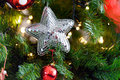 Spangled christmas star silver hanging on the branch of a tree amongst sparkling lights and baubles for a festive Royalty Free Stock Photography