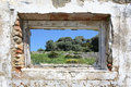 Spanish countryside seen through hole in wall of ruins Stock Photos