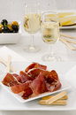 Spanish cuisine serrano ham jamon serrano tapas sliced in a white plate two glasses of sherry wine in the background selective Stock Images