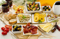 Spanish cuisine variety of tapas on white plates assortment including serrano ham manchego cheese marinated olives pikles potatoes Royalty Free Stock Photo