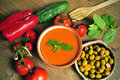 Spanish gazpacho a bowl with some vegetables to prepare it such as tomato red pepper and cucumber and a plate with gazpachas Royalty Free Stock Images