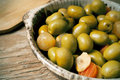 Spanish olives closeup of an earthenware plate with on a rustic wooden table Royalty Free Stock Photo