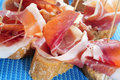 Spanish pincho de jamon spanish ham served on bread typical a blue background Royalty Free Stock Image