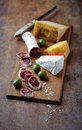 Spanish salami brie hard cheese rustic wooden board Stock Photo