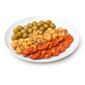 Spanish tapas plate of with chorizo sausage salted jumbo corn and pimento stuffed olives isolated on a white background Stock Photos