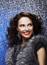 Sparkle beautiful fashion model with shiny earrings in fur vest toothy smile woman brilliant vaistcoat Stock Image