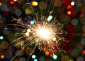 Sparkler burning on festive background decorated christmas tree Stock Photo