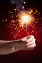 Sparkler in hand close up view red background Stock Photography