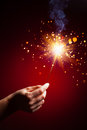 Sparkler in hand close up view red background Royalty Free Stock Photography