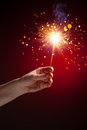 Sparkler in hand close up view red background Royalty Free Stock Images
