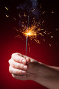 Sparkler in hand close up view red background Royalty Free Stock Photos