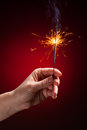 Sparkler in hand close up view red background Stock Image