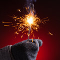 Sparkler in hand mitten close up view red background Stock Image