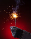 Sparkler in hand mitten close up view red background Royalty Free Stock Photography