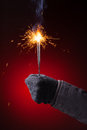 Sparkler in hand mitten close up view red background Stock Photos