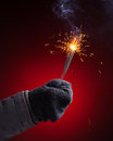 Sparkler in hand mitten close up view red background Stock Images