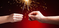 Sparklers in hands close up view red background Royalty Free Stock Image