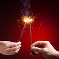 Sparklers in hands close up view red background Stock Photo