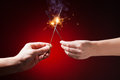 Sparklers in hands close up view red background Royalty Free Stock Photo