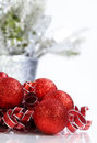 Sparkling red christmas ornaments and curly ribbons on reflective white surface Stock Photography