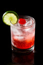 Sparkling red cocktail refreshing with water and ice garnished with a lime and cherry Royalty Free Stock Photo