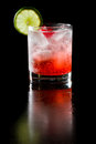 Sparkling red cocktail refreshing with water and ice garnished with a lime and cherry Stock Image