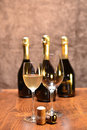 Sparkling wine a full glass of white and an empty one two corks on a wooden table and four full bottles on the background Royalty Free Stock Images