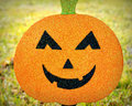 Sparkly pumpkin face a orange and black smiling against a grassy background Royalty Free Stock Photos
