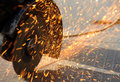 Sparks from an angle grinder cutting through metal and are flying Stock Photos