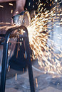 Sparks while grinding worker cutting metal using angular machine Stock Photo