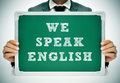 We speak english a man wearing a suit holding a chalkboard with the sentence written in it Stock Images