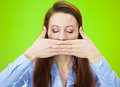 Speak no evil closeup portrait of young woman covering closed mouth closed eyes concept isolated on green background negative Royalty Free Stock Images